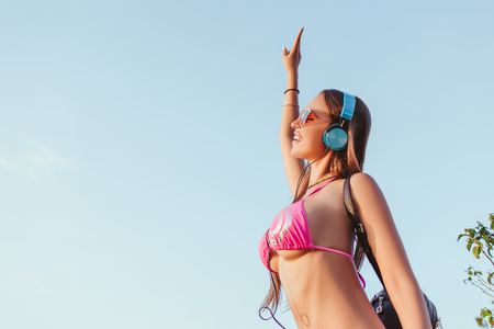 low angle view of attractive girl in headphones and pink bikini dancing against blue sky Banco de Imagens