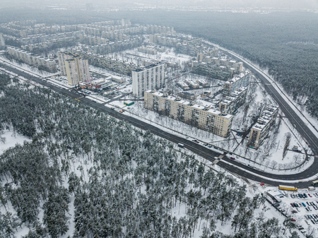 aerial view of apartment buildings on snowy streets surrounded with forest, Kyiv, Ukraine