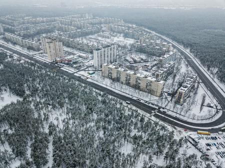 luchtfoto van flatgebouwen op besneeuwde straten omgeven door bos, Kiev, Oekraïne