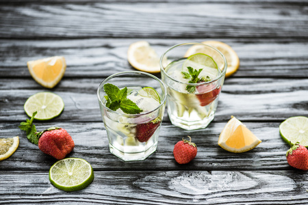 high angle view of delicious strawberry mojito cocktail in glasses on wooden table