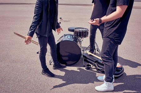 partial view of rock band in black clothing standing near musical instruments on street Stock Photo