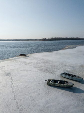 aerial view of river bank with boats covered with snow, Kyiv, Ukraine