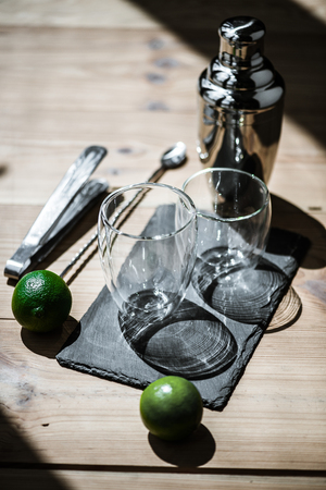 close-up view of fresh limes, empty glasses, tongs and shaker on wooden table
