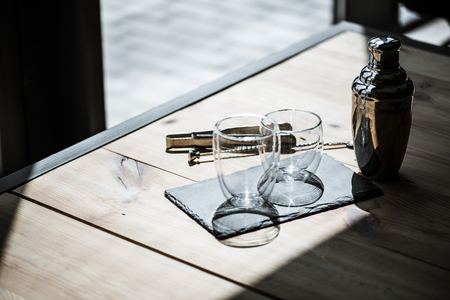 high angle view of shiny empty glasses on slate board, shaker and tongs on wooden table 스톡 콘텐츠
