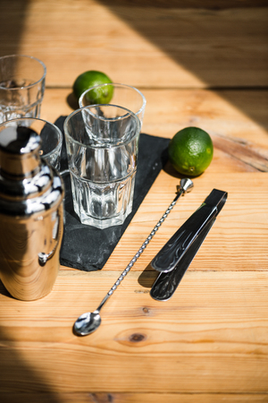 high angle view of empty glasses, shaker, tongs and fresh limes on wooden table Stockfoto