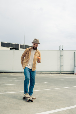 stylish bearded man holding disposable coffee cup and skateboarding on street