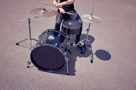 cropped shot of tattooed drummer playing drums on street Фото со стока - 107250374