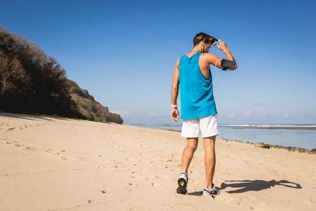 back view of sportsman walking on seashore, Bali, Indonesia Stock Photo