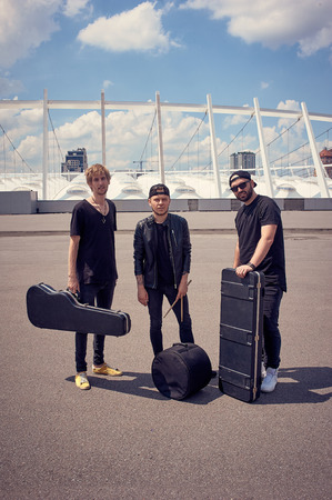 rock music band with musical instruments in cases standing on street Фото со стока