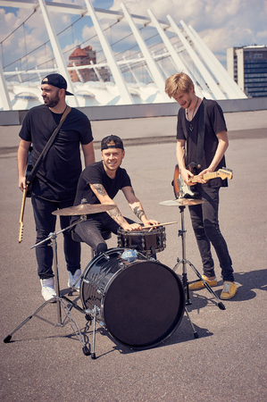 rock band in black clothing with musical instruments on street