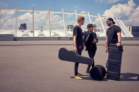 rock music band with musical instruments in cases having conversation on street Фото со стока