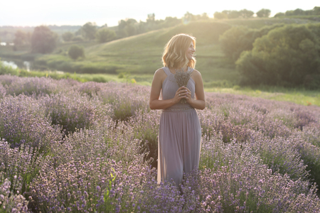 attractive woman standing with small bouquet in violet lavender field