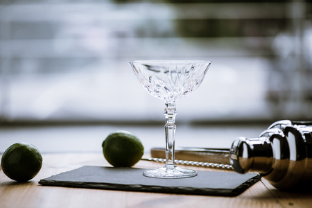 close-up view of margarita glass on slate board, shaker and limes on wooden table