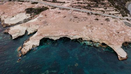 aerial view of sandstone rocks on seashore with blue water, Cyprus