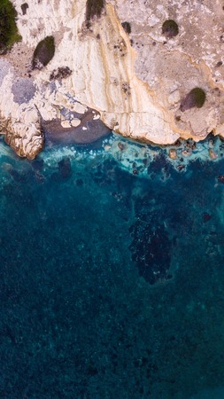 aerial view of beautiful sandstone rocks on seashore with blue water, Cyprus Фото со стока