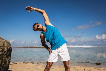 sportsman in sunglasses stretching on beach near sea Stock Photo