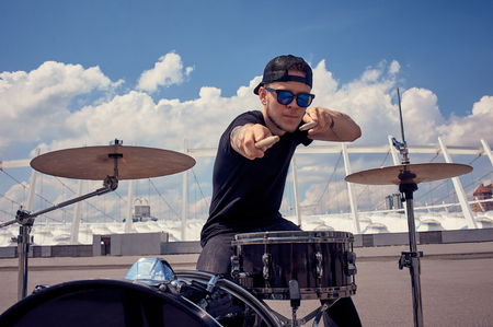 young tattooed drummer in sunglasses playing drums on street