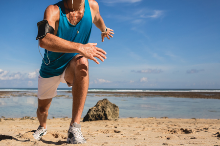 cropped view of sportsman with armband doing lunges on beach near sea