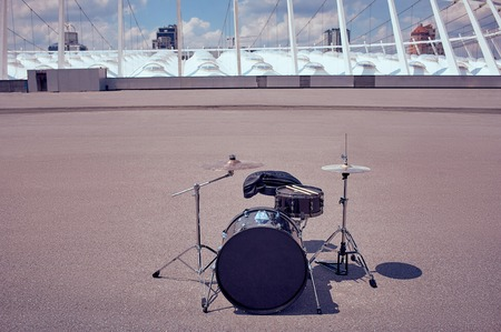 close up view of black drum kit and drum sticks on street