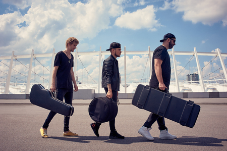 side view of rock music band with musical instruments in cases walking on street with cloudy sky on background Фото со стока