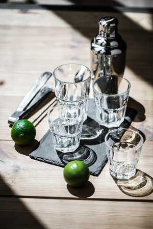 high angle view of fresh limes, empty glasses, tongs and shaker on wooden table