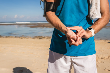 cropped view of sportsman counting pulse on wrist after training Stock Photo
