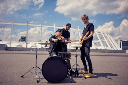 rock band in black clothing playing music on street