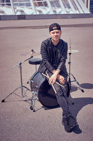 drummer in black clothing with drum sticks sitting on drum kit on street