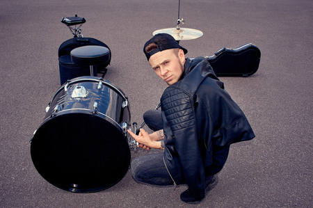 Drummer in black clothing pointing at drum kit on street Stockfoto