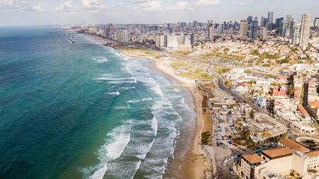 widok z lotu ptaka na duże miasto z piaszczystym brzegiem morza i falującym morzem, Tel Awiw, Izrael