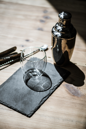 close-up view of shiny empty glass on slate board, shaker and tongs on wooden table Stock Photo