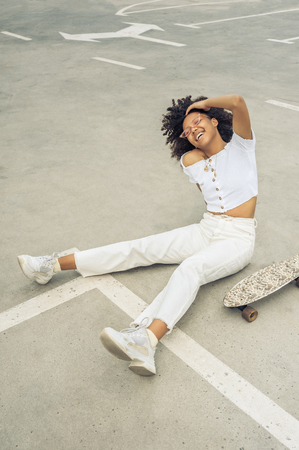 high angle view of cheerful african american girl sitting near skateboard and laughing on street