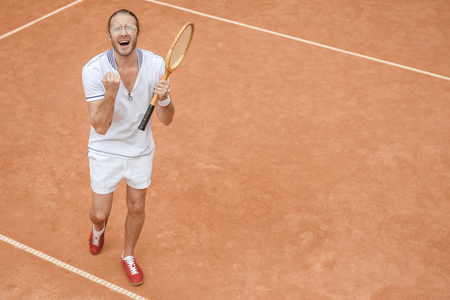 handsome emotional winner with racket yelling and celebrating on tennis court Banco de Imagens - 107584575