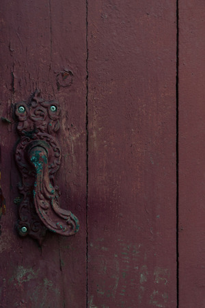 close-up view of vintage decorative door handle on old wooden door