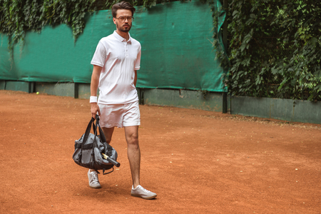 handsome tennis player walking with bag after training on tennis court