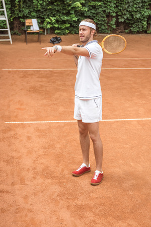 handsome retro styled tennis player in white sportswear with wooden racket pointing on court