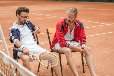 athletic friends with wooden rackets sitting on chairs after training on tennis court