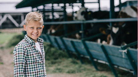 boy in checkered shirt smiling at camera while standing at ranch with cows