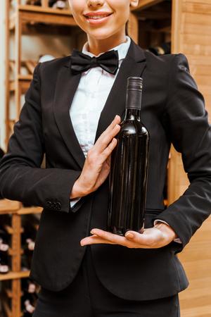 cropped shot of female wine steward holding bottle at wine store Stock Photo