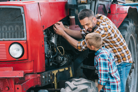 happy father and son repairing tractor engine together Stockfoto