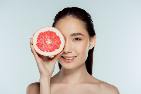 attractive asian girl posing with grapefruit, isolated on grey