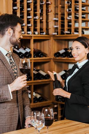 female wine steward showing bottle of luxury wine to customer at wine store