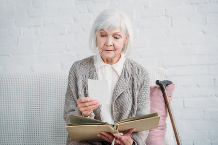 portrait of grey hair lady looking at photos from photo album while resting on couch at home