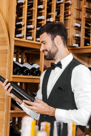 smiling young sommelier looking at bottle of wine at wine store Stock Photo