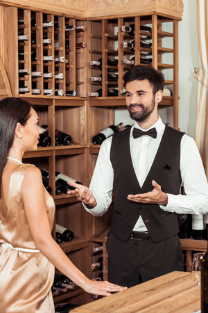 wine steward chatting with beautiful female customer at wine store