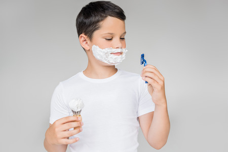 portrait of preteen boy with razor, brush shaving foam on face isolated on grey 写真素材