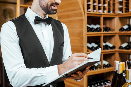cropped shot of smiling young wine steward making notes at wine store Stock Photo
