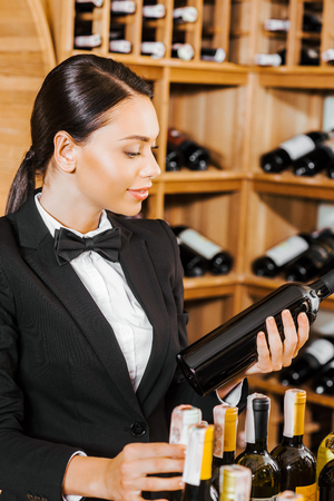 attractive female wine steward with wine bottles at wine store Stock Photo