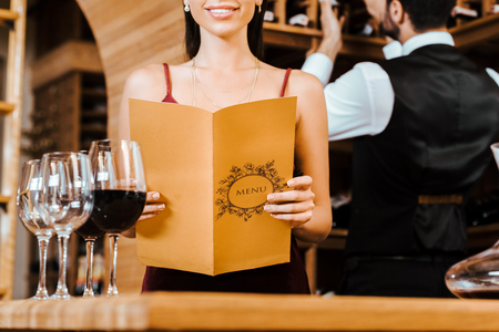 cropped shot of smiling woman holding menu card at wine store while steward taking bottle from shelf on background