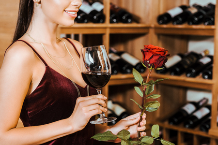 cropped shot of beautiful woman in red dress with wine and rose at wine store Reklamní fotografie